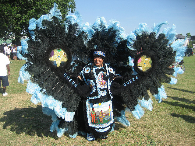 Mardi Gras Indian dressed in hand-crafted suit of black and blue feathers.